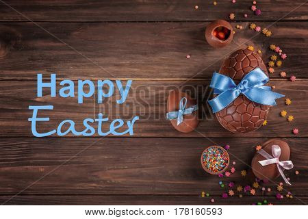 Delicious treats and text HAPPY EASTER on wooden background