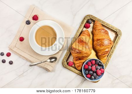 An overhead photo of a cup of coffee with fresh raspberries, blueberries, and croissants