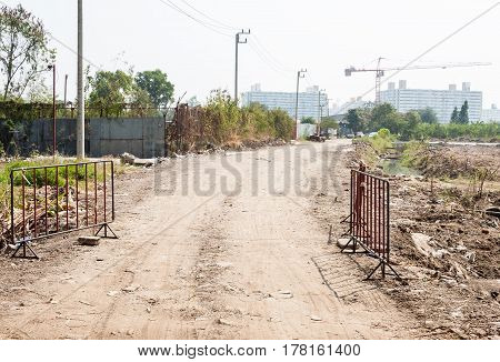 Dirt road with the metal barrier to the construction site.