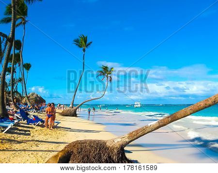 Punta Cana, Dominican republic - February 02, 2013: The Ordinary tourists resting at the Caribbean Sea and coconut palms and white sand of the tropical beach of Punta Cana, Dominican republic