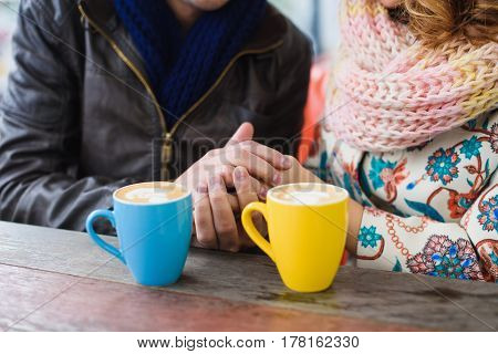 Man and woman drinking coffee. Street Cafe. Closeup of couple hands with yellow and blue cups.