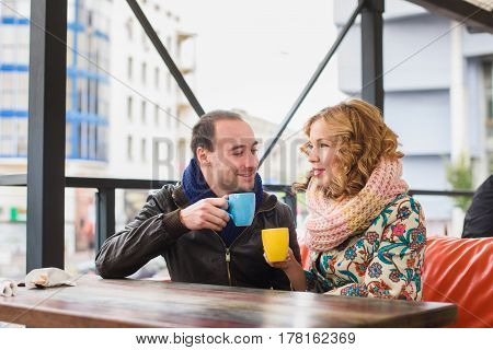 Man and woman drinking coffee. Street Cafe. Couple with yellow and blue cups.