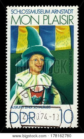 GERMANY - CIRCA 1974: a stamp printed in the Germany, Democratic Republic (DDR)  shows painting by Manfred Gottschall, crier of a show booth, Castle Museum Of Arnstadt