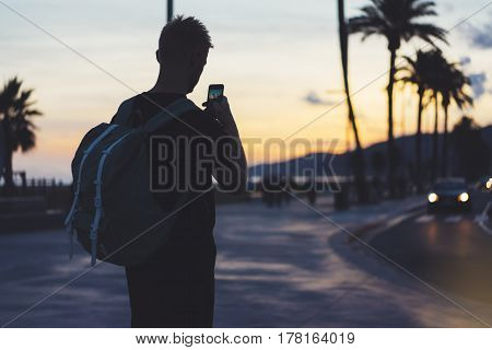 Man with backpack making photo sunset beach on smart phone tourist look and enjoy nature on background color sky and taxi on palm summer street hipster using in hands mobile phone traveler mock up