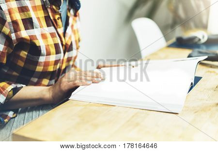 Young girl reads book during breakfast and coffee female hands close up flipping through magazine pages in home relax atmosphere room on background of natural wooden table woman is studying mock