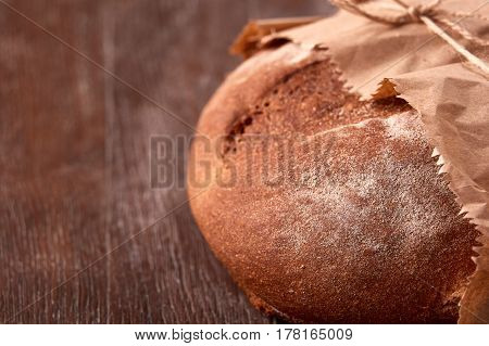 Loaf of rye bread in paper bag on wooden table. Bakery background. Decorative rope. Flour. Brown background. Tasty and appetizing.