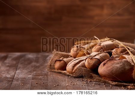 different bread on the wooden table, paper bags, burlap, rope and ears of wheat with brown blurred background. Delicious food. Fresh baking. Tasty and appetizing. Angle position.