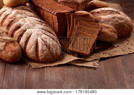Freshly baked bread loaves on burlap on wooden table with wheat. Texture closeup bakery products. Slice of bread on the board.