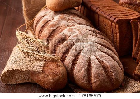 Different kinds of bread on burlap on the wooden table. Kitchen or bakery poster design. With wheat and ears of wheat. Slice of the braed on the board. Tasty food.