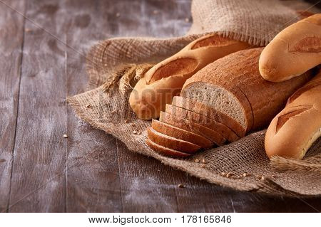 Slices of bread and baguette on burlap on the dark wooden table, Space for text. With wheat and ears of wheat. Flour. Delicious food. Fresh baking. Tasty and appetizing.