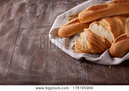Slices of white bread and baguette laying on white cloth with gradient dark-brown background. Wooden table. With flour and wheat. Delicious. Tasty food.