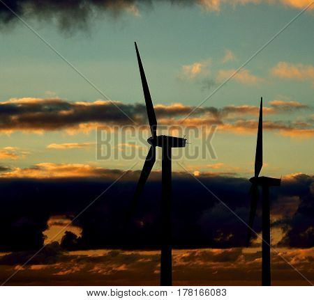 Wind farm backlit with dramatic sky before sunrise