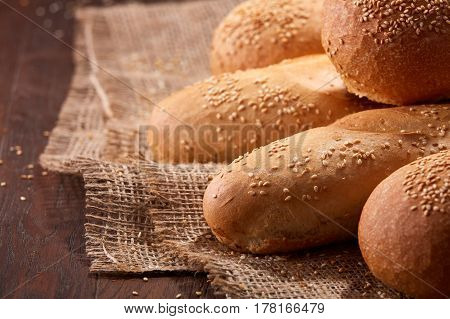 Freshly baked baguette bread and rulls on a burlap napkin on a wooden background. Close up. Delicious food. Fresh baking. Tasty and appetizing.