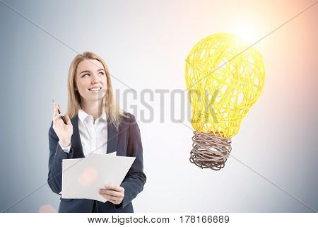 Portrait of a smiling blond woman with documents standing near a gray wall with a big light bulb on it. Toned image