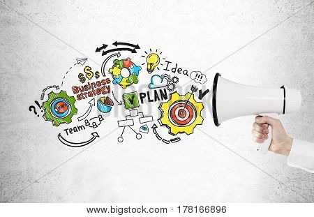 Close up of a hand of a buisnessman in a white shirt holding a megaphone near a concrete wall with a colorful business plan drawing.