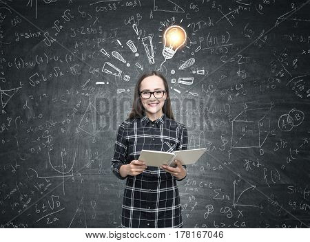 Portrait of a smiling nerdy girl wearing glasses and a black checkered shirt and holding a book while standing near a blackboard with a light bulb and exclamation marks.