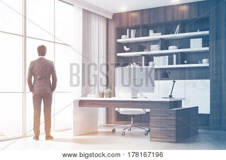 Rear view of a company CEO standing in his dark wood office with a bookcase a massive table and a computer. 3d renedirng. Toned image