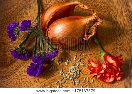 Appetizing array of flowers and foods with shallots,fennel seeds and carnation