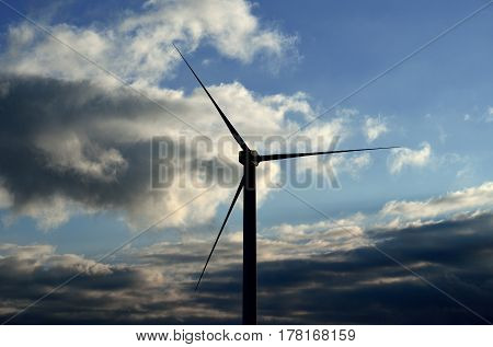 Wind turbine isolated with clouds background at dawn