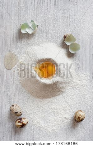 Sifted Flour And Quail Eggs On The Light Wooden Table