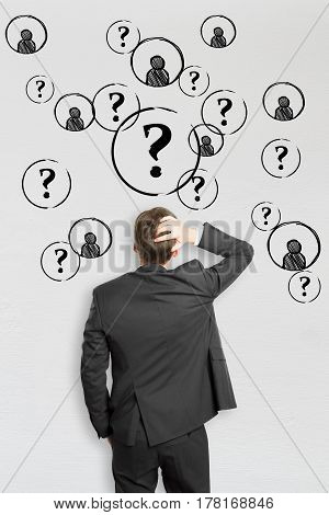 Back view of stressed young businessman on concrete background with question marks and HR icons. Hiring concept