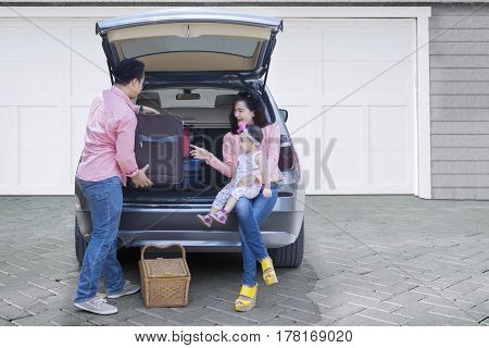 Photo of happy Asian family preparing for road trip and summer vacation with their car