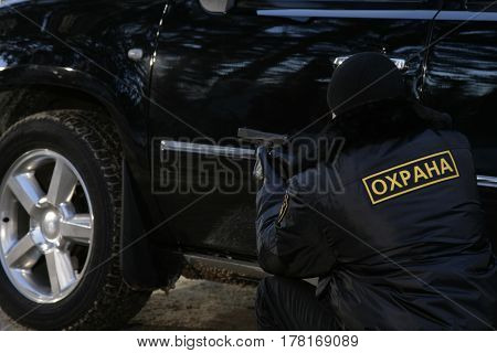 The bodyguard hides behind the car with a gun in his hands