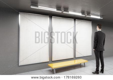 Thoughtful businessman in underground interior with three ad posters and bench. Advertisement concept. Mock up 3D Rendering