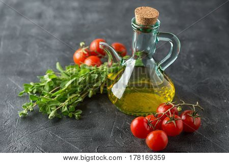 Ingredients for Italian cuisine - a bottle of vegetable oil marjoram and cherry tomatoes on a dark background