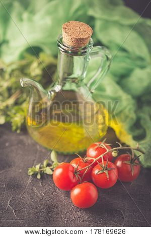 Ingredients for Italian cuisine - a bottle of vegetable oil marjoram and cherry tomatoes on a dark background. Toned Photo.