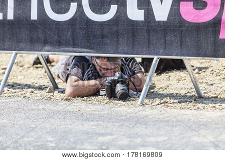 Le Mont Saint Michel, France-July 10 2013: Image of a sport photographer looking to the camera's screen while lying in the dust on the roadside, during the stage 11 of the edition 100 of Le Tour de France 2013.