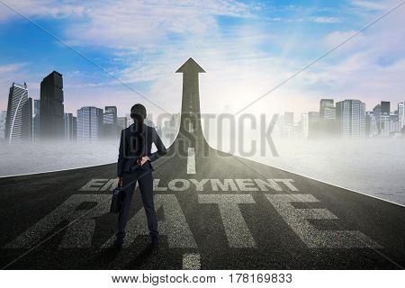 Image of young businesswoman standing on the road with employment rate text and upward arrow