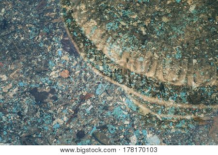 Abandoned fountain with coins and garbage. Old stone decorative fountain. Abstract background.