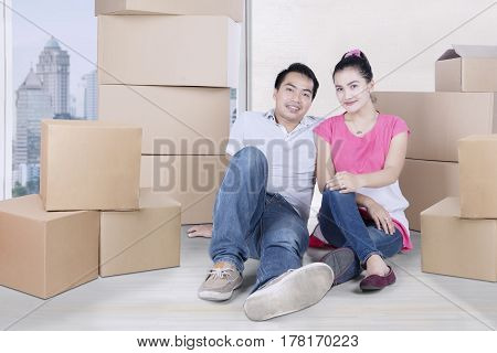 Picture of a beautiful wife and her husband sitting with piles of cardboard while resting in new apartment