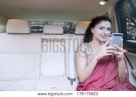 Young Indian woman sitting inside a car while wearing saree clothes and using a mobile phone. Shot in traffic jam