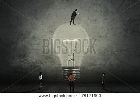 Young male manager standing on a bright lightbulb and calling his subordinate with a megaphone