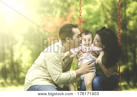 Two young parents kissing their daughter on a swing at the park