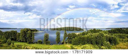 Rainbow in summer over the Stroust lake in Braslav region of Belarus. Panoramic image