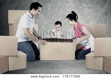Image of happy parents with their daughter are unpacking cardboard while kneeling on the floor