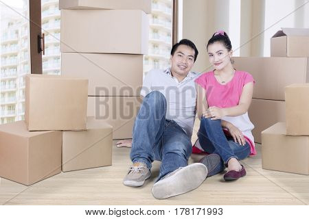Picture of romantic couple sitting with boxes on the wooden floor while looking at the camera