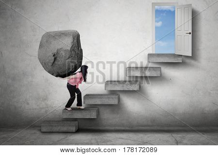 Picture of a strong businesswoman brings a big stone on her back while climbing a stairs toward a doorway