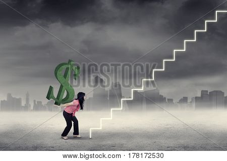 Strong businesswoman bringing a big dollar symbol on her back while walking toward a stairs