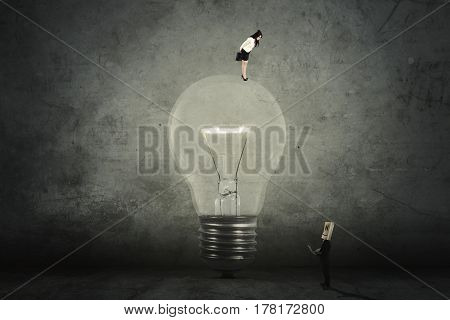 Female entrepreneur standing on a bright light bulb and looking down at her worker