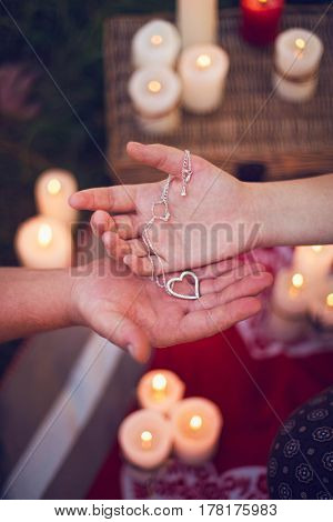 A chain with a heart in the hands and a guy and a girl in the background of candles