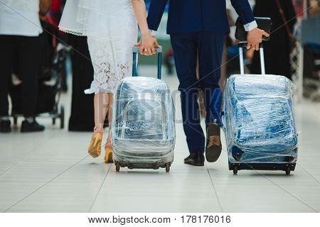 Newlyweds fly away on a honeymoon. In the airport go with suitcases