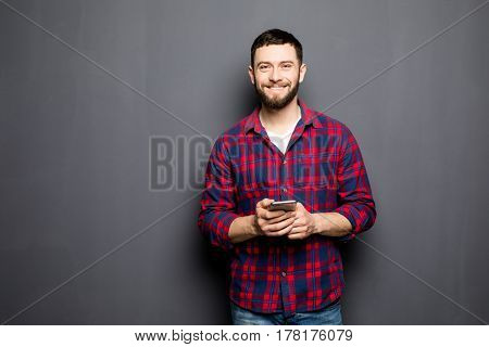 Confident Young Man Holding Smart Phone And Looking At Camera While Standing Against Grey Background