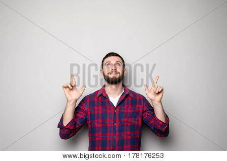 Happy Young Man In Shirt Pointing Up And Looking At Up. Isolated Gray Background