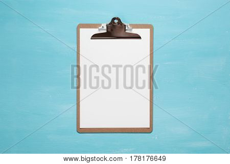 Blank clipboard on pastel blue color background with copy space, minimal style, flat lay.