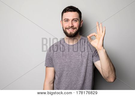 Portrait Of A Cheerful Young Man Showing Okay Gesture