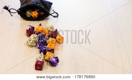 Colorful roleplaying dice scattered on a table with a linen dice pouch